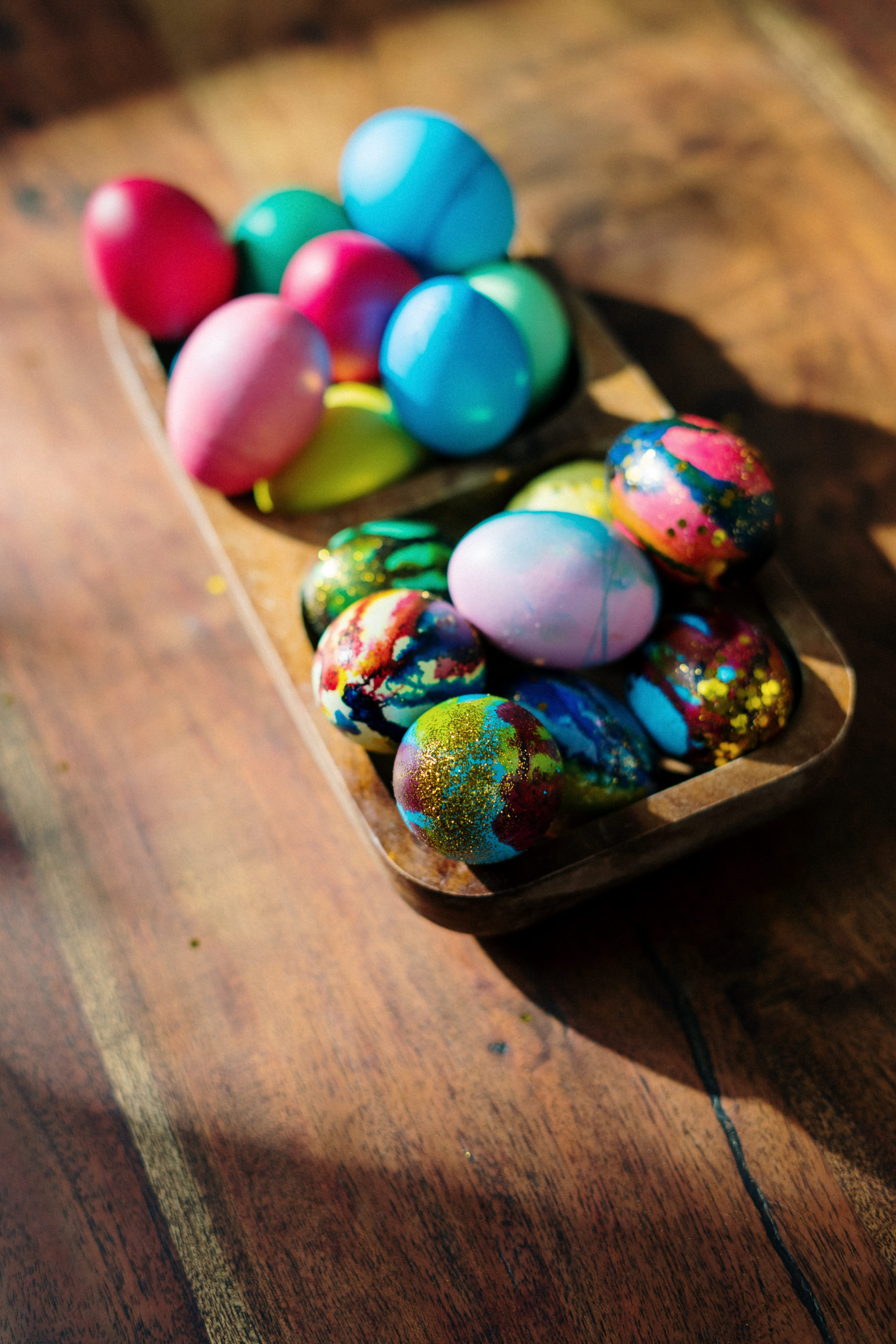 Assorted easter eggs on brown wooden tray