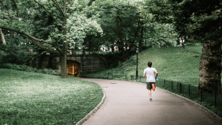 Photo of man jogging on paved pathway